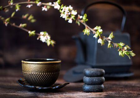 Schwarzer Gusseisenkessel, Zen-Steine und eine Tasse. Tee asiatisches Konzept