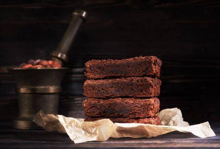 Pieces chocolate brownie cake on a dark wooden background