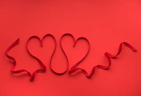 Two red hearts of red ribbon. Valentines day greeting card