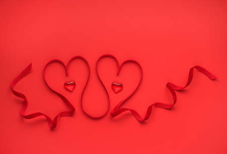 Two red hearts of red ribbon. Valentines day greeting card festive background