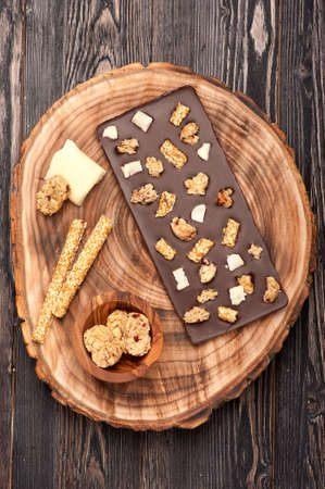 Handmade chocolate with cookies, sesame seeds and nuts