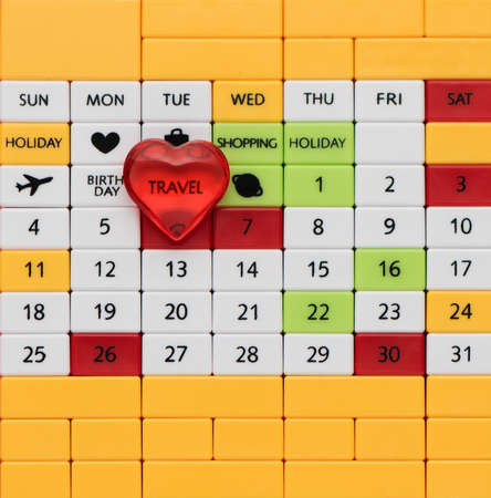 Perpetual calendar background with inscription travel and red heart, top view, close-up. Planning, vacation and travel concept