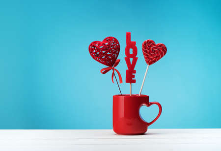 Happy Valentine's Day Creative greeting card with candies in a red cup with hearts, copy space. Valentine day festive background.