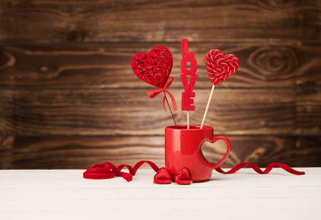 Valentine's Day Creative greeting card with candies in a red cup with hearts and chocolates on a wooden background, copy space. Valentine day festive background.
