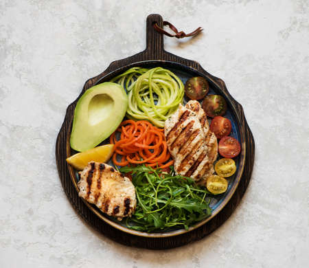 Salad with grilled chicken fillet, arugula, avocado and fresh vegetables, balanced clean food, top view. Balanced food concept. Healhty lunch bowl.