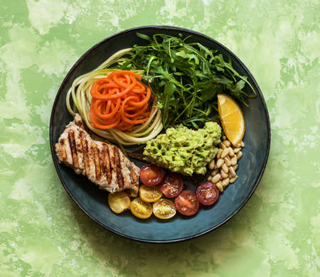 Balanced food concept. Buddha bowl salad with grilled chicken breast, arugula, avocado, carrots and zucchini, balanced clean eating, top view. Healhty lunch bowl. Stockfoto