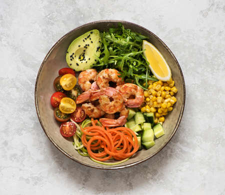 Buddha bowl salad with grilled prawns, arugula, avocado, corn, tomatoes and cucumbers. Ð¡lean eating, top view. Healhty lunch bowl. Balanced food concept. Stockfoto