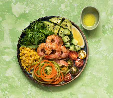 Buddha bowl salad with grilled shrimp, fresh vegetables and herbs. Ð¡lean eating, top view. Healhty lunch bowl. Balanced food concept.