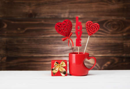 Valentine's Day festive card with candies in a red cup with a heart and a gift on a wooden background, copy space. Valentine day background.