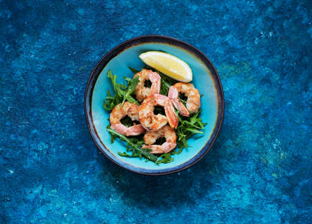 Salad with arugula and fried shrimp. Seafood balanced clean eating, top view. Healhty lunch bowl. Stockfoto