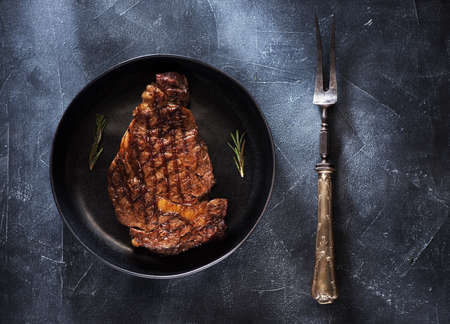 Ribeye steak on a plate and vintage meat fork, top view Stockfoto