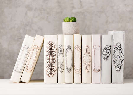 Old books and flower in gray concrete vase on on wooden shelf with copy space