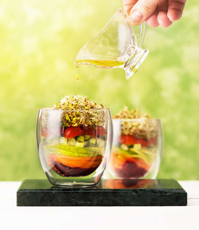 Salad in glass with microgreens and fresh vegetables. Healthy food, diet, detox, clean eating and vegetarian concept