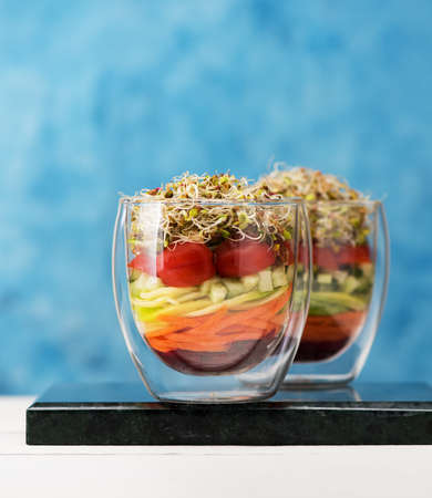 Healthy Salad in glass with microgreens and fresh vegetables. Healthy food, diet, detox, clean eating and vegetarian concept