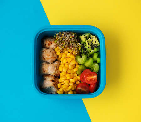 Grilled turkey, avocado, fresh vegetables and sprouts with olive oil in a container, top view. Ð¡lean eating concept. Balanced healthy diet. Stockfoto