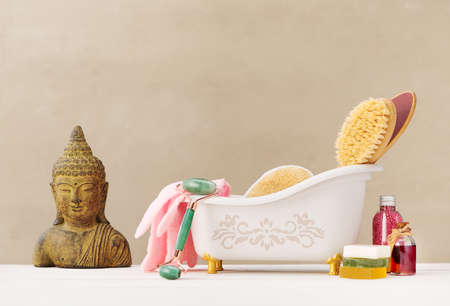 Spa and body care concept. Natural massage brush, gua sha massage roller, and Natural Organic cosmetics products in a vintage dispenser on a light background.