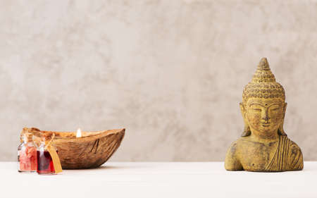 Head of Buddha and candle with aroma oil and sea salt on a light background. Spa, meditation, relaxation and aromatherapy concept.