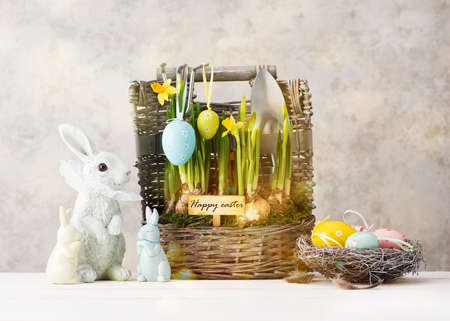 Easter festive card with Easter eggs, colorful Bunny and yellow spring flowers in a basket on white wooden table. Easter concept.