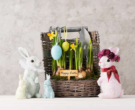 Happy easter festive card with Easter eggs, Bunnies and beautiful spring flowers in the basket. Easter concept