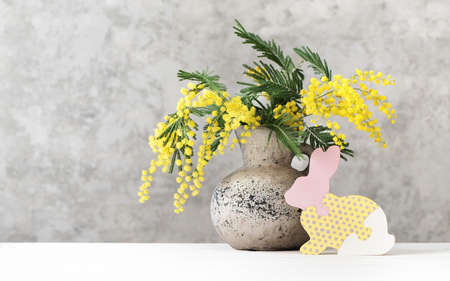 Happy Easter background with beautiful spring bouquet mimosa in vase and wooden bunny. Easter concept with copy space.