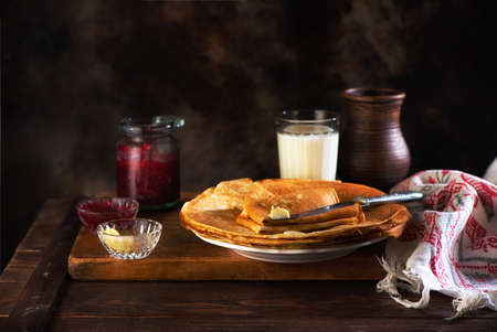 Thin pancakes with raspberry jam and butter on a wooden table