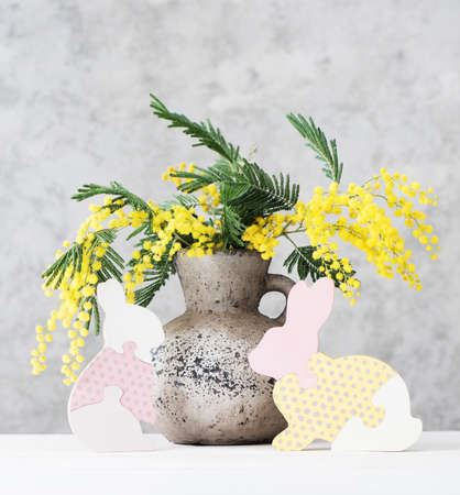 Happy Easter holiday card with beautiful spring bouquet in vase and funny wooden bunnies. Stockfoto