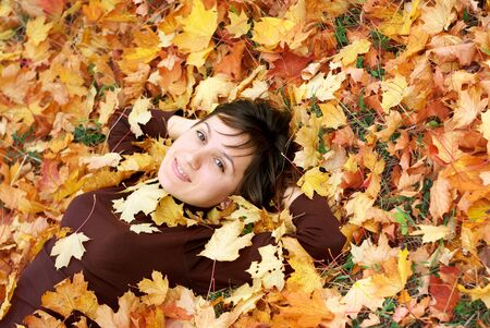 Girl in autumn leafs. Emotional scene. photo