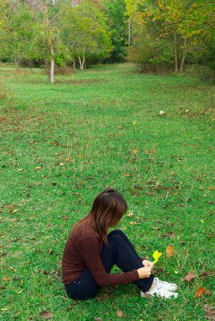 Girl sits  in meadow. Emotional scene. photo