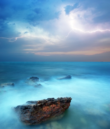 lightning storm: Rocks and sea storm. Dramatic scene. Composition of nature
