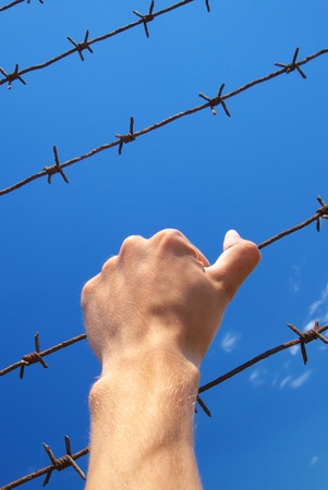 penal institution: Hand of prison and sky background. Conceptual scene. Stock Photo