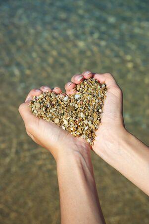 Símbolo de corazón en la mano femenina. Diseño conceptual.  Foto de archivo