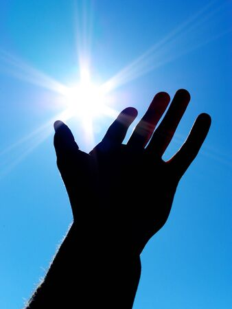 Sun on palm. Silhouette of human hand. Concept design. photo