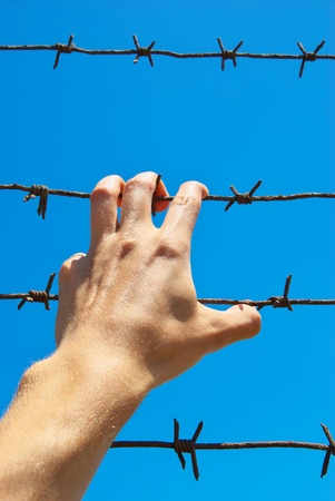 penal institution: Hand of prison and sky background. Conceptual scene.