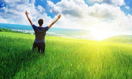 rising sun: Man in meadow green meadow. Emotional scene. Stock Photo
