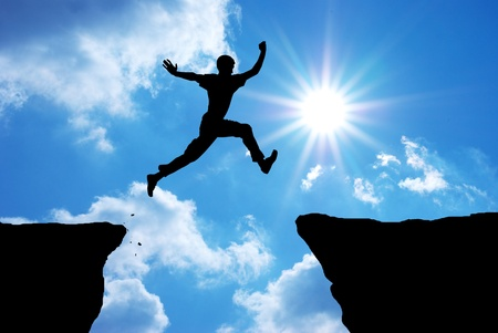 cliff top: Man jump through the gap. Element of design.