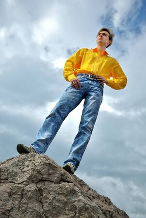 Man in yellow shirt on the  top of mountain. Stock Photo - 8931945