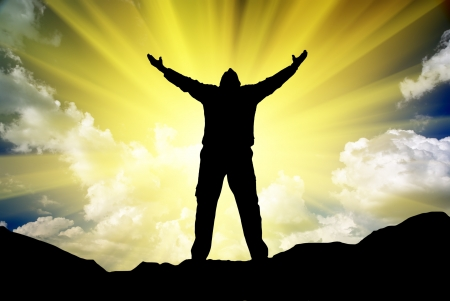 victory: Silhouette of man and sunshine on sky background.