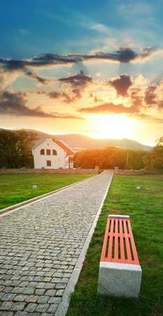 Road, bench, and house on the sunset. Landscape composition. photo