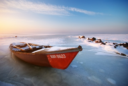 Boat on ice. Winter landscape composition.