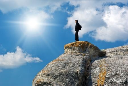 cliff top: Man on the peak of mountain.  Stock Photo