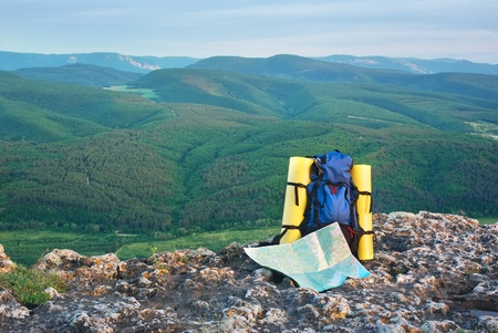 Backpack and map in mountain.  photo