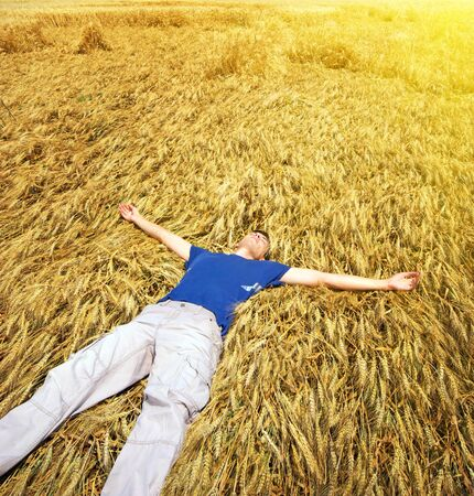 lie down: Man lie down in yellow meadow.