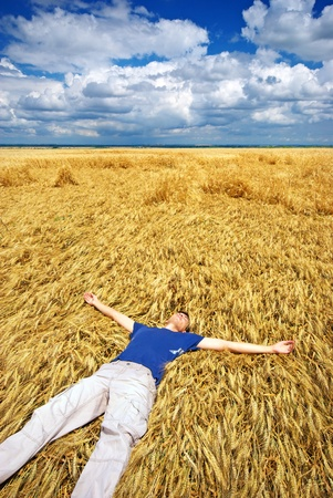 sun down: Man lie down in yellow meadow.