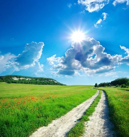 Carril en una pradera y el cielo azul profundo. La naturaleza del diseño. Foto de archivo