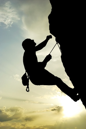 Silhouette of climber at the sunset. Element of design.  photo
