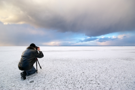 Photographer in work at winter on ice. photo
