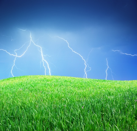 Lightning and green meadow. Nature composition. photo