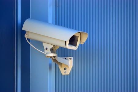security: Security camera on the blue wall.