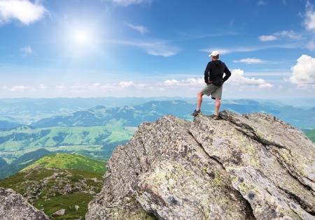 Man on peak of mountain  Conceptual design Stock Photo - 25062865