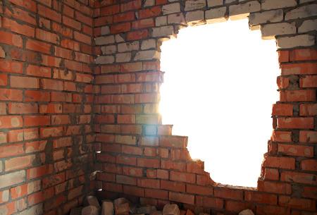 the hole: Broken bricks wall. Conceptual composition.